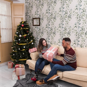 Guy presenting gift to lady on settee near christmas tree