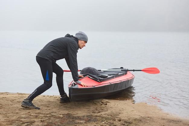 Парень толкает лодку в воду, смотрит на туманную реку в теплой одежде.
