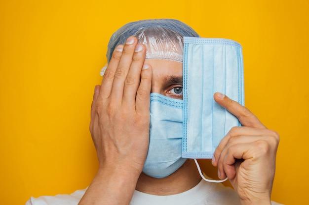 男は彼の目の上に呼吸マスクを着用します。魅力的な男性がマスクを着用し、カメラを見ています。風邪、インフルエンザ、ウイルス、扁桃炎、急性呼吸器感染症、検疫、流行の概念。