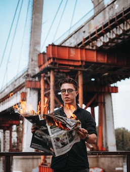 Guy reads a burning newspaper in front of a bridge