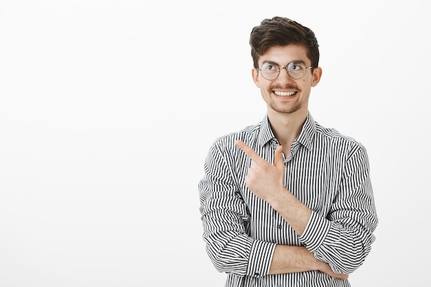 Guy recalled funny moment. portrait of interested good-looking european male freelancer in glasses, pointing at upper left corner and smiling broadly, thinking about joke, standing over gray wall