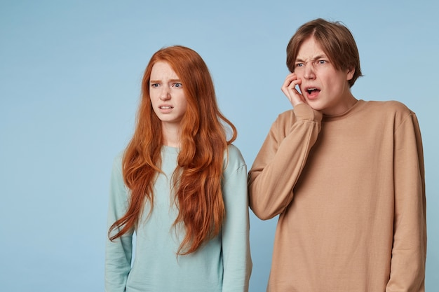 A guy and a red-haired woman are standing sideways looking distance look at something unpleasant