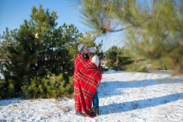 Guy in the red plaid blanket wraps the girl up so she gets warm