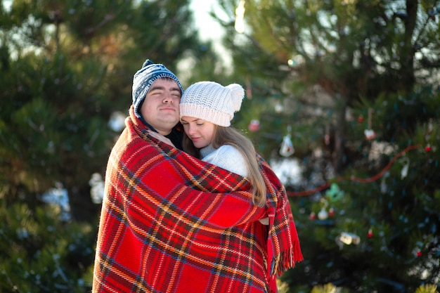 The guy in the red plaid blanket wraps the girl up so she gets warm