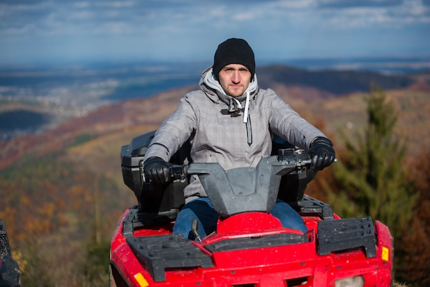 Guy on red quad bike on the blurred background nature at sunny day