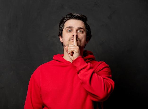Guy in red sweatshirt show quiet gesture on dark wall
