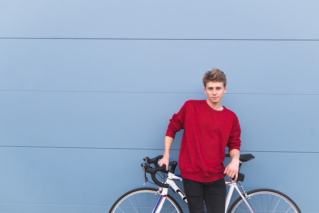 Guy in a red sweatshirt standing with a white bike on the background of a blue wall