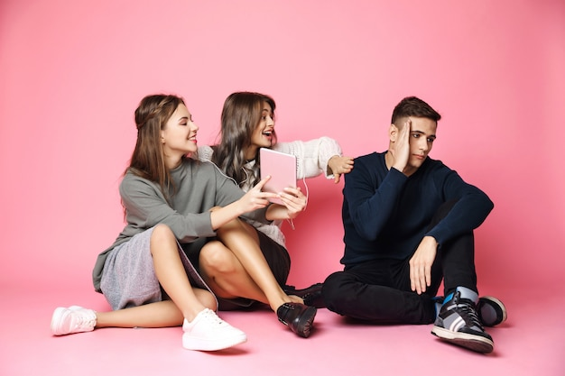Guy refuse to look in tablet. friends sitting on pink floor