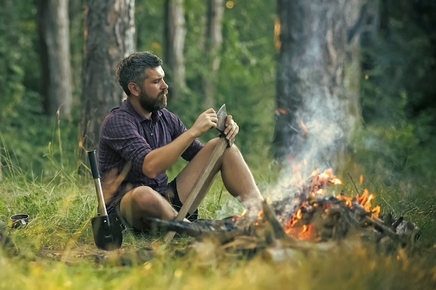 Guy relax at bonfire in forest.