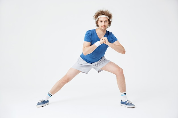 Guy in retro sport suit doing stretching exercises. white