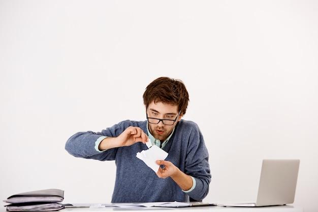 Il ragazzo strappa documenti e fissa con espressione curiosa e interessata, fa il buffone al lavoro, impazzisce dalle scadenze