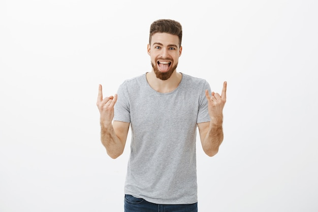 Guy rocking on party brings positive vibes. carefree amazed and happy caucasian handsome charismatic male with beard, blue eyes showing tongue showing rock-n-roll gesture enjoying cool music in club