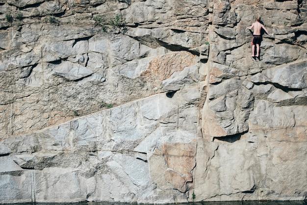 Парень лазает по скалам и выглядит сверху, экстремально. хохлатая поверхность, в трещинах