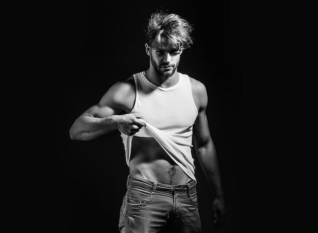 남자, 흰색 조끼와 바지에 섹시한 젊은 남자 모델은 벌거 벗은 근육질 몸통과 가슴이 검은 색 바탕에 있습니다. 프리미엄 사진