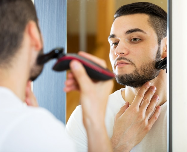 Guy shaving by electric shaver
