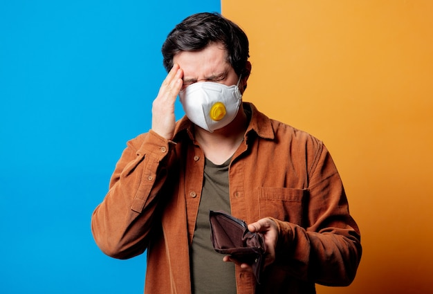 Guy in shirt and ffp2 face mask hold empty wallet on yellow and blue background
