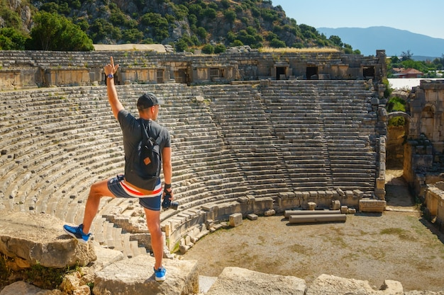 The guy in shorts, a gray t-shirt,a black cap and a backpack stands on the background of an ancient amphitheater with a raised hand and a finger up