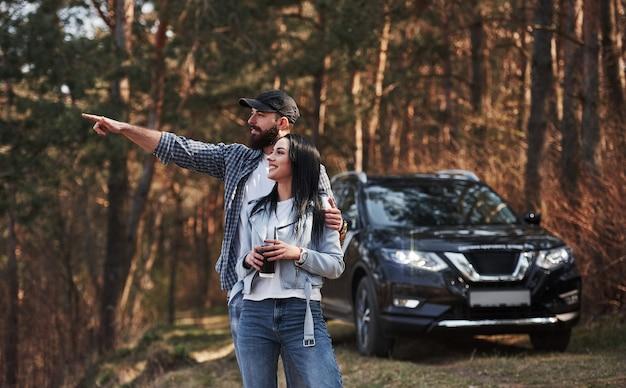 뭔가 아름다운 것을 보여주는 남자. 자연을 즐기고 있습니다. 부부가 새 검은 차를 타고 숲에 도착했습니다.
