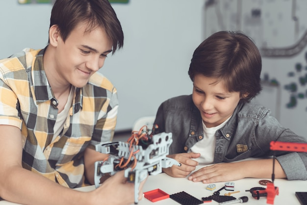 The guy shows the boy how the robot is arranged