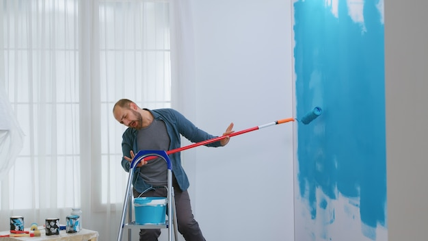 Guy singing during home repair using roller brush dipped in blue paint. hipster renovating his house. apartment redecoration and home construction while renovating and improving. repair and decorating