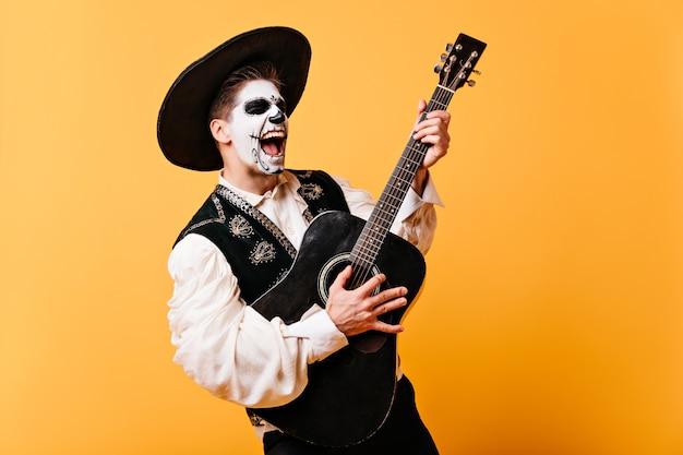 감정적 인 노래를 부르는 남자는 기타를 연주합니다. 솜브레로에 그려진 얼굴을 가진 남자의 초상화,