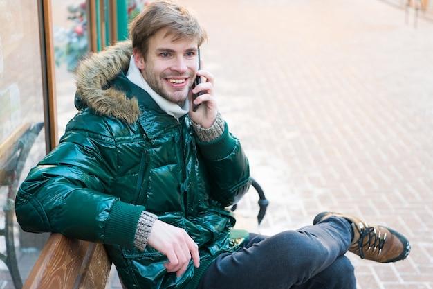 男はベンチに座ってスマートフォンを操作します。コミュニケーションの概念。流行に敏感な人は冬の日にスマートフォンを使用します。男ハンサムホールドスマートフォン。無精ひげを生やした男は暖かいジャケットを着て、スマートフォンの雪に覆われた都会の背景を保持します。