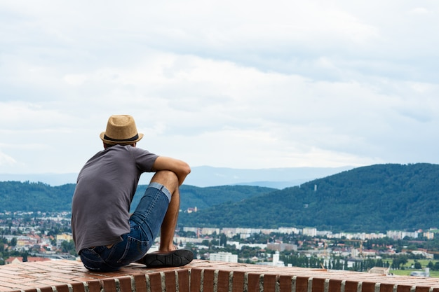 Guy sit on the edge of a tall building and looks into the distance