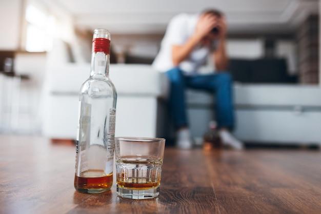 男はソファに座って二日酔いや頭痛に苦しんでいます。アルコールは強い飲み物を飲むことに問題があります。