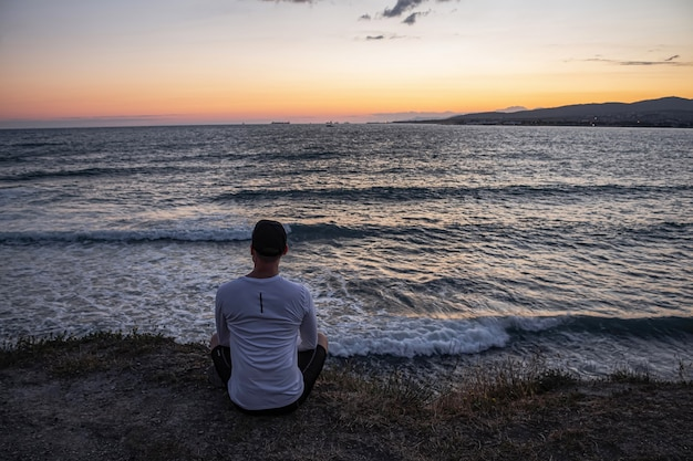 Guy sits on the edge of a cliff and looks at the beautiful seascape and waves. rest and meditation after a long workout.