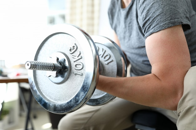 Guy sits at home and lifts heavy metal dumbbells