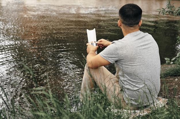 男は都市公園に座って自然を楽しんでいます