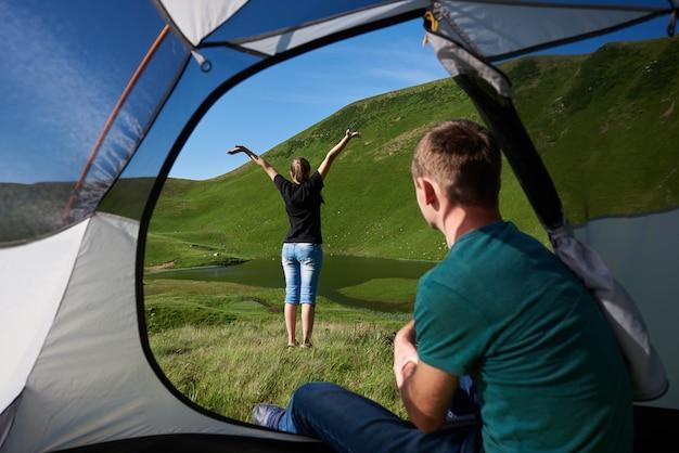 男はテントの中に座っており、彼のガールフレンドは青空の下で力強い緑の山のふもとにある澄んだ湖の景色を楽しんでいます。テントの中からの眺め