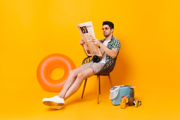 Guy sits and reads newspaper on space of suitcase, pineapple and rubber ring.