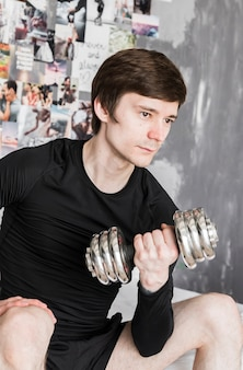 Guy sitting and exercising with dumbbell