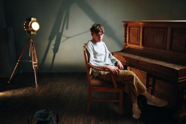 Парень сидит возле пианино, позирует в центре внимания студии