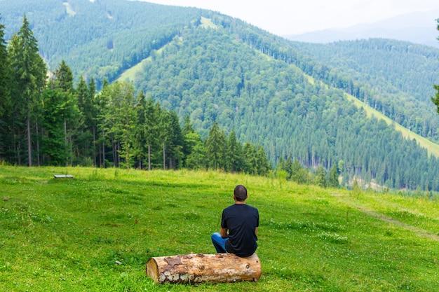 Парень сидит на бревне и наслаждается мирным пейзажем зеленых гор. душевное спокойствие и расслабление.
