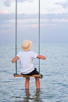 Парень сидит на качелях и положил ноги в воду и смотрит на море