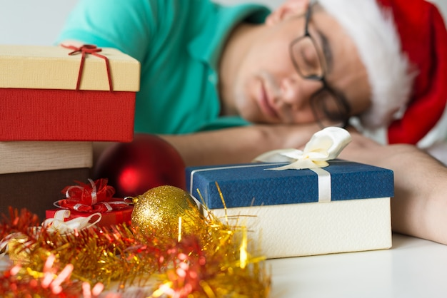 Guy sleeping on table with christmas gifts and baubles