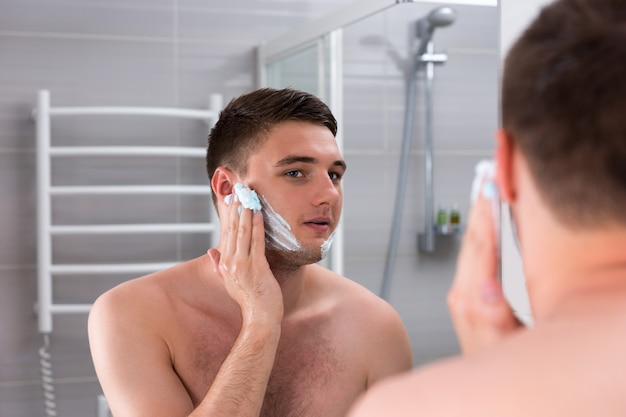 집에 있는 현대적인 타일 욕실에서 거울 앞에 서 있는 얼굴에 면도 젤을 바르는 남자