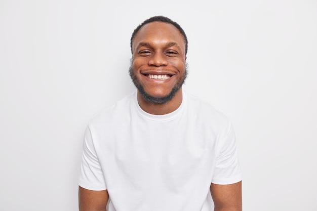 Il ragazzo sorride a trentadue denti sembra felicemente felice di ricevere elogi vestito con abiti casual isolati su bianco