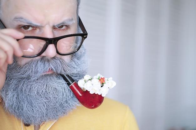 담배 파이프를 피우는 남자. 회색 수염과 콧수염이 있는 소식통. 나쁜 습관