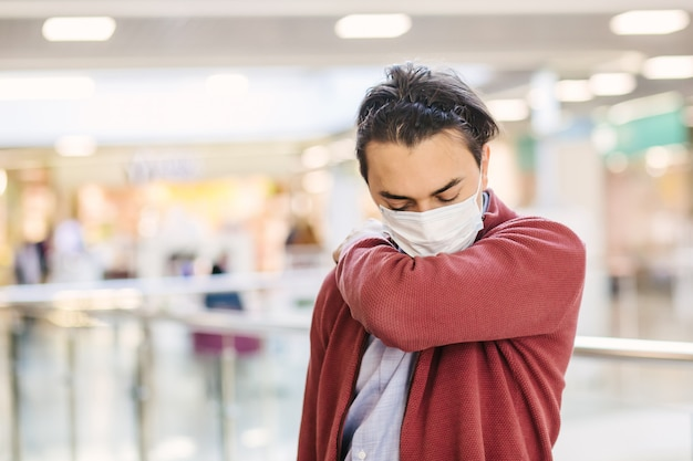 Guy sneezes in the elbow.