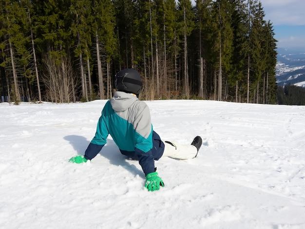 雪の中で座ってスキーの後に休んでいる男のスノーボーダー