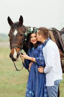 Guy softly kisses a pretty woman with a wreath on her head who holding a horse for a bridle