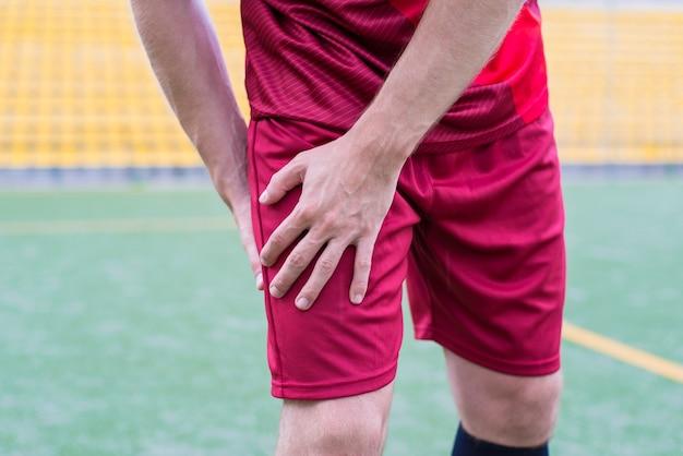 Guy in sportswear holding hip