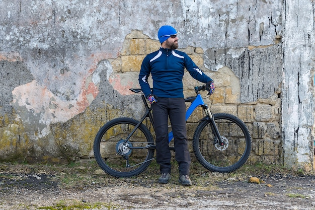 A guy in sportswear riding clothes on a modern mountain carbon bike with an air suspension fork