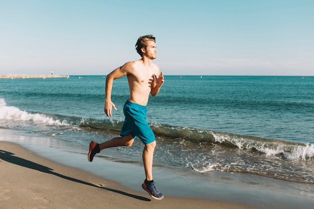 Guy sprinting at the beach