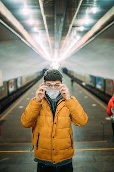 Парень стоит на станции в медицинской защитной маске на лице