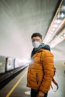 彼の顔の医療保護マスクで駅に立っている男
