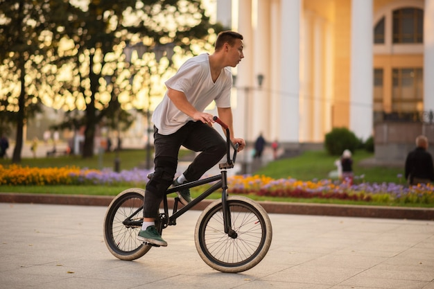 The guy, standing at full height, rides a bmx bike. for any purpose.